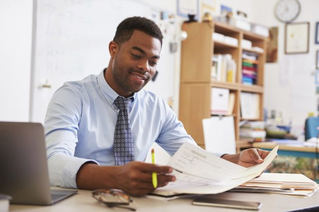 Young male teacher at his desk