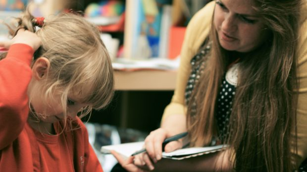 Female teacher helping pupil with school work