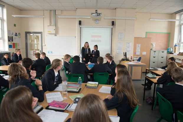 Two secondary pupils presenting at the front of a classroom