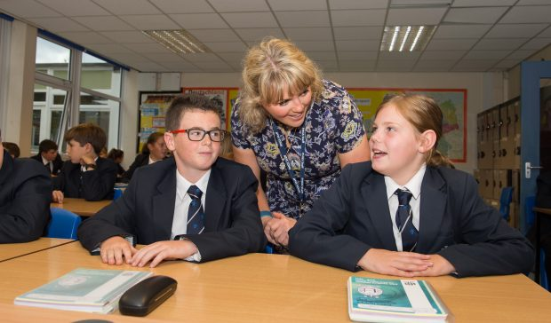 Teacher talking to two secondary pupils during a lesson