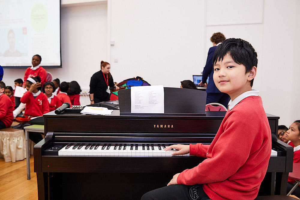Primary school pupil is sat at a Yamaha digital piano.