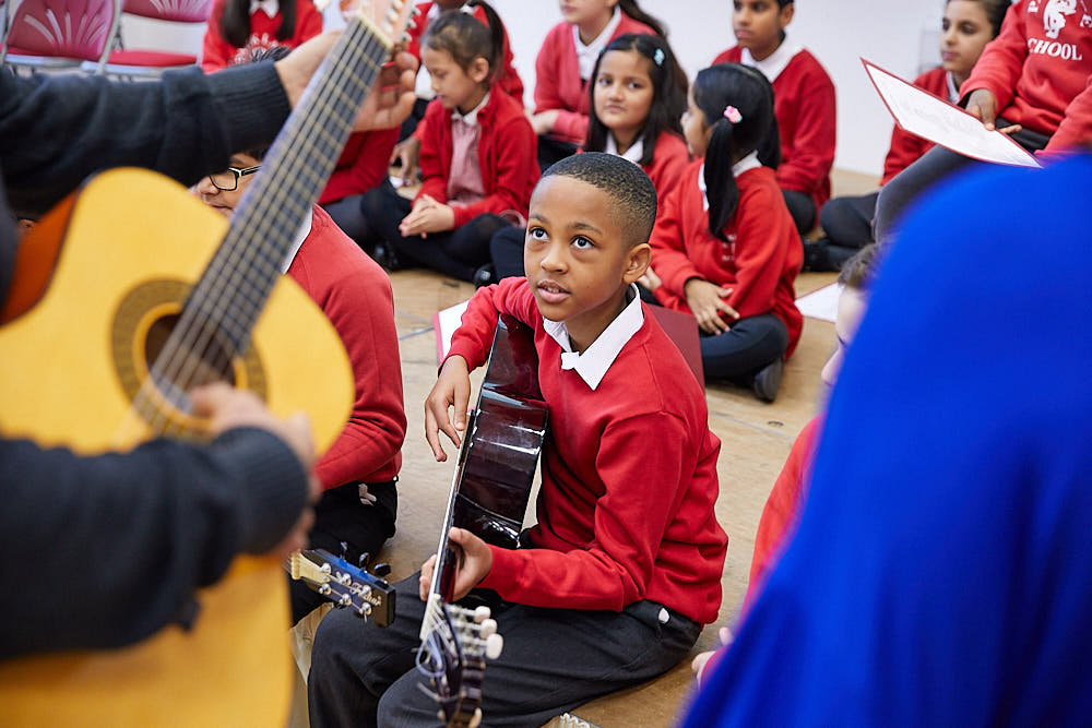 A group or primary school children sat on the floor, being taught how to play the guitar.