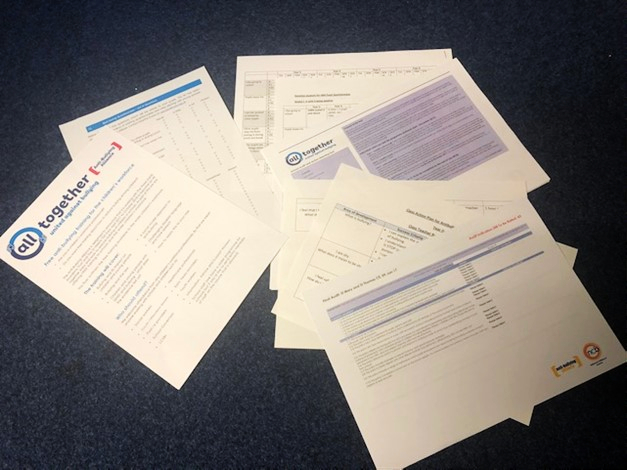 Several documents on the floor, detailing the all together programme guidance.
