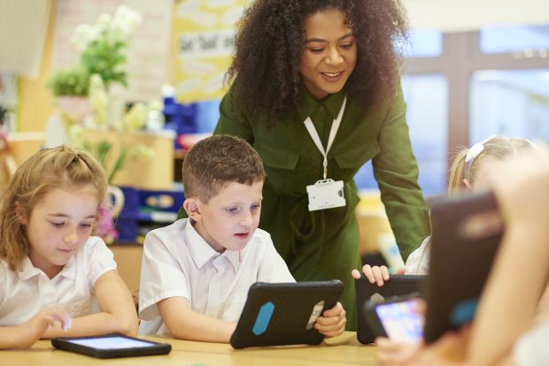 A teacher stands over a group of school children whilst they use tablets.