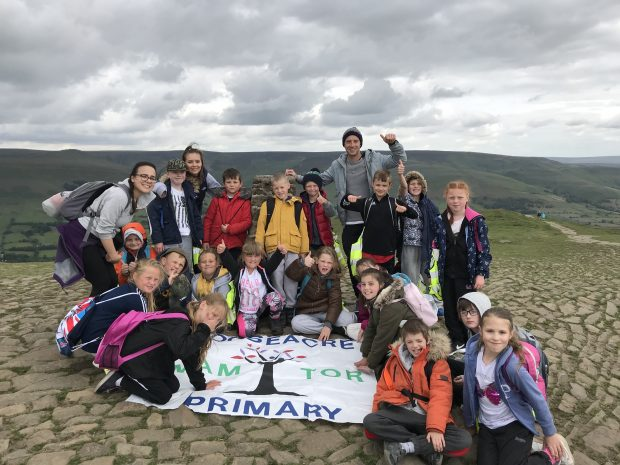 Group of children from Gooseacre Primary celebrating being at the top of Mam Tor.