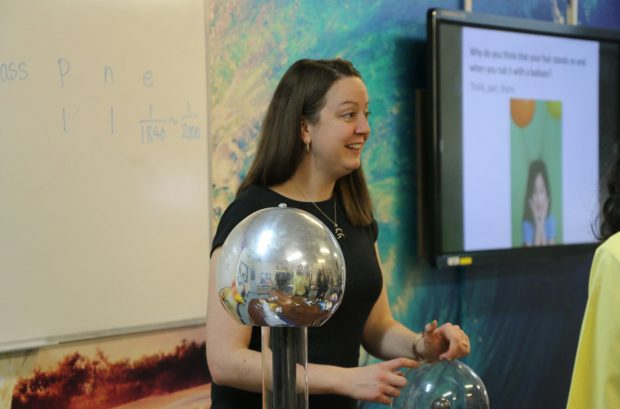 Emma Russo, physics teacher leading a class using silver physics object
