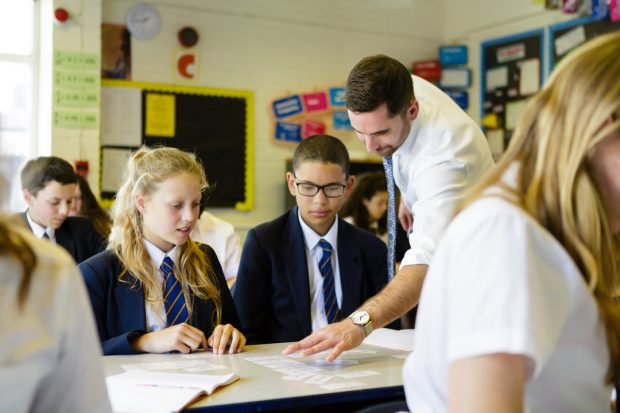Teacher helping two pupils in the classroom