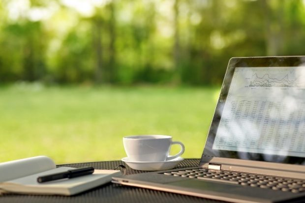 A laptop and a mug of tea sit on a table in a garden