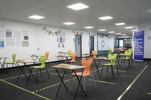 A large school room with single desks spaced evenly apart with yellow and black tape marking the boundaries in on the floor.