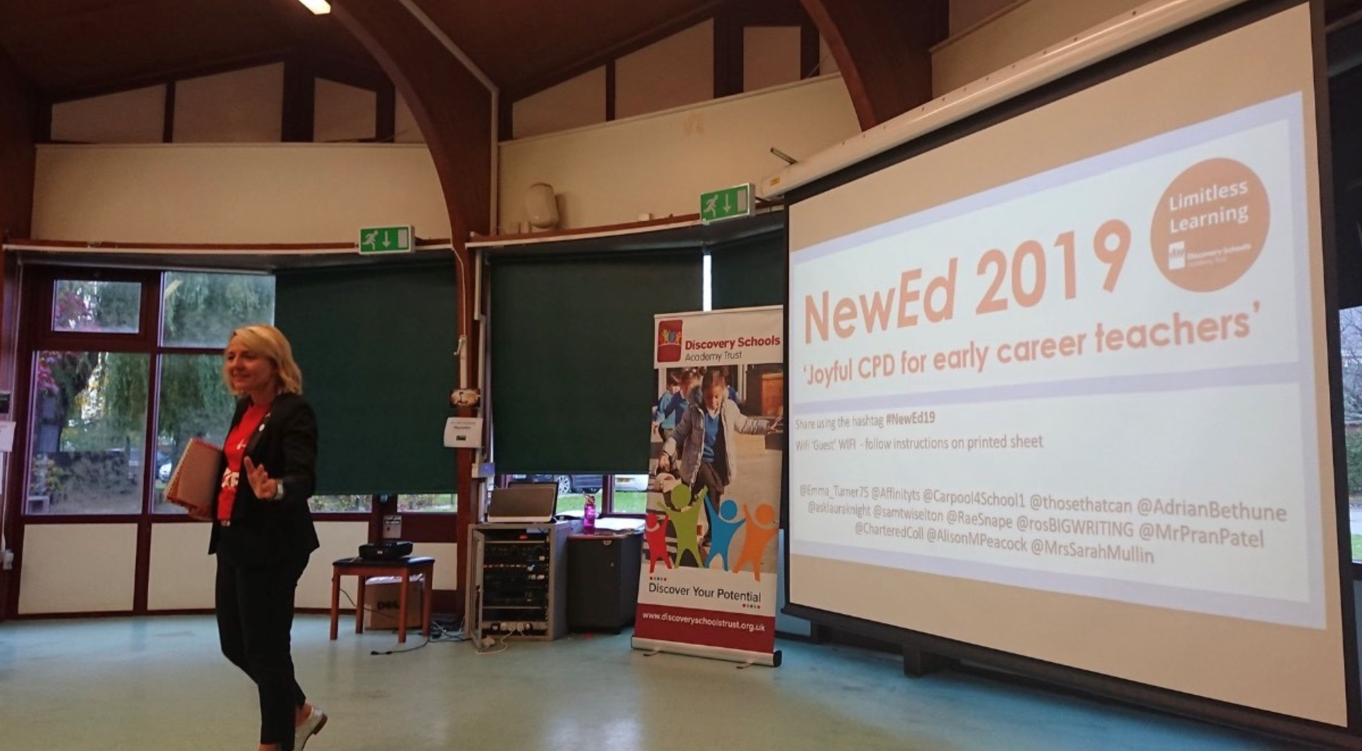 Emma Turner delivering a presentation in front of a powerpoint reading 'NewEd 2019'