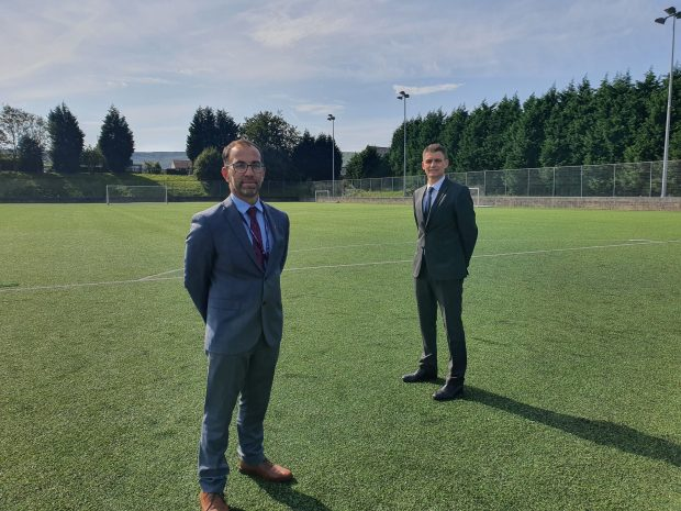 Two men stand 2m apart on a school field facing the camera