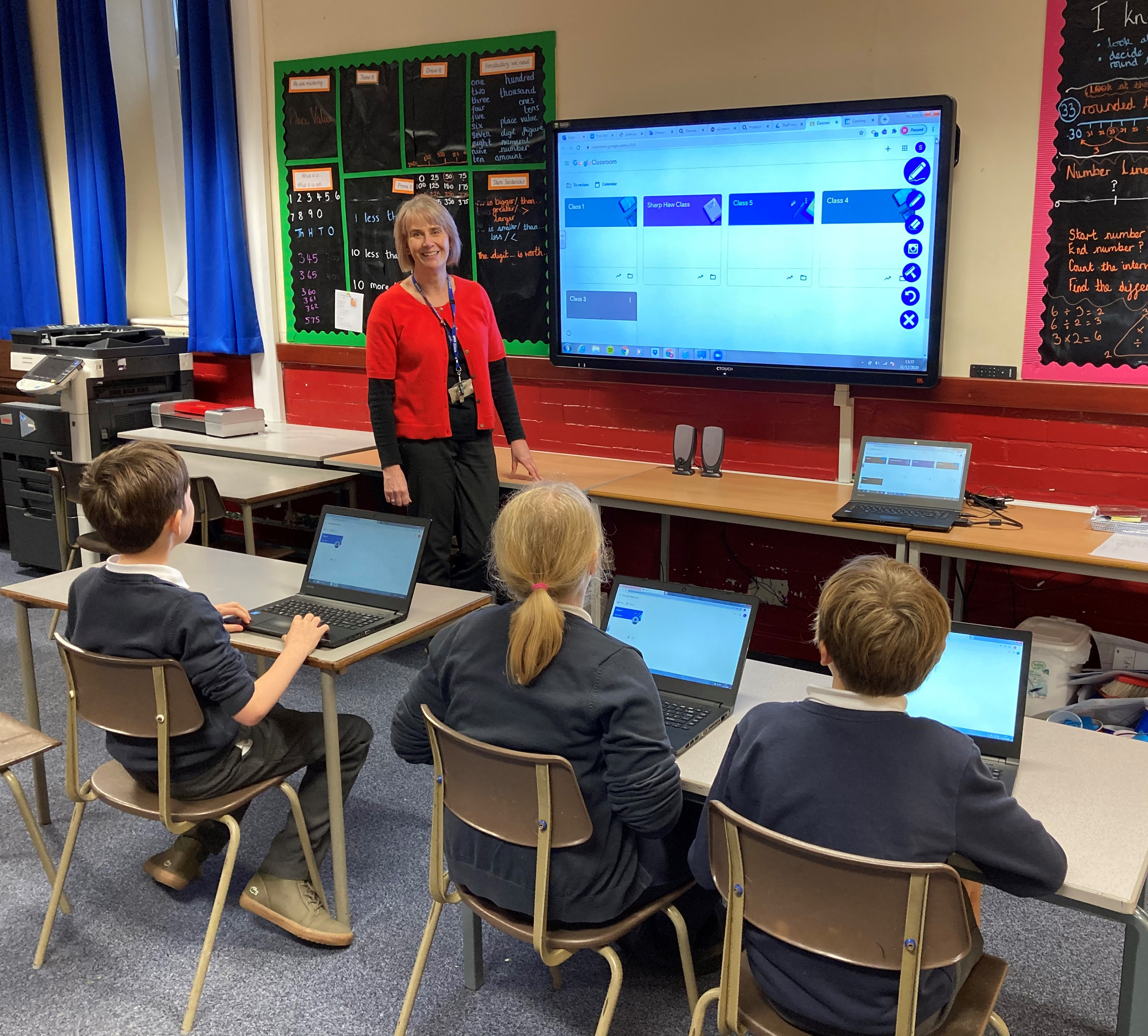 A teacher at the front of a classroom smiles at the camera, three primary pupils sit at desks with laptops
