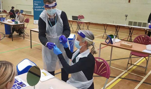 Adults wearing gloves, plastic visors and aprons sit in a sports hall, one handing a syringe to the other