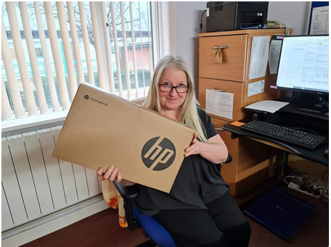 A blonde woman, Terri Wyse, with new laptop box