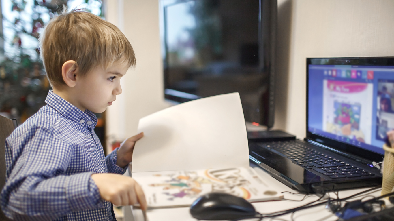 Distant education, online class meeting. Young boy studying during online lesson at home