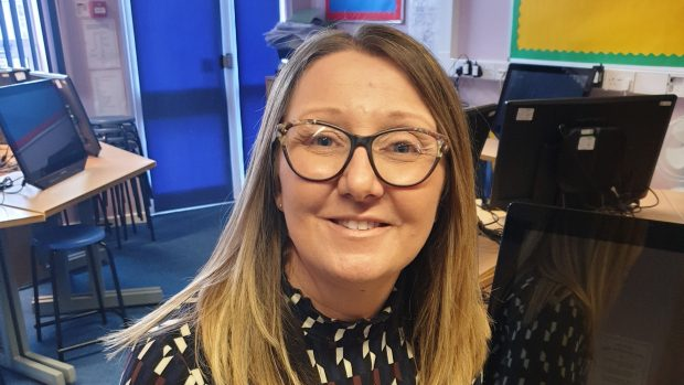 A young woman wearing glasses smiles at the camera
