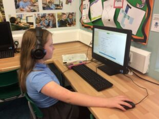 Young girl wearing headphones working at a computer