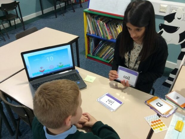 Academic mentor working with a young boy on phonics